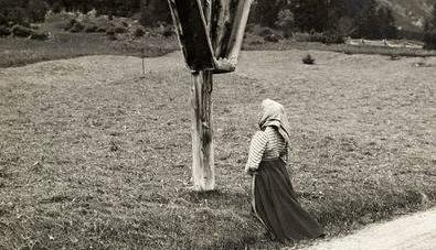 Jeune chrétienne priant devant un calvaire, avec une tenue intégralement chrétienne.